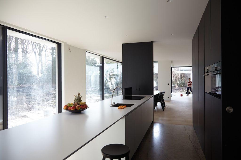 cocina con gola, columnas en fresno negro e isla lacada en blanco polar seda